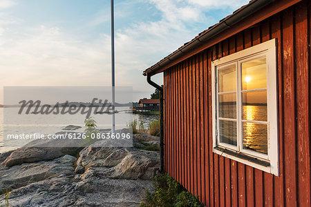 Sweden, Uppland, Stockholm archipelago, Nasslingen, Reflection of sun in window at sunset