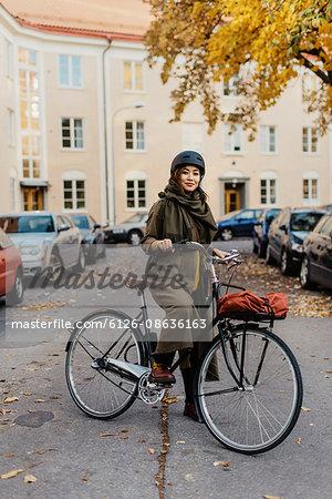 Sweden, Uppland, Stockholm, Vasastan, Rodabergsbrinken, Young woman standing with bicycle