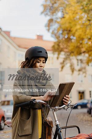 Sweden, Uppland, Stockholm, Vasastan, Rodabergsbrinken, Young woman using digital tablet standing by bicycle