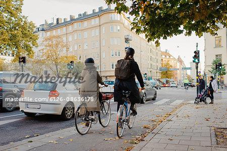 Sweden, Uppland, Stockholm, Vasatan, Torsgatan, Man and woman cycling on city street