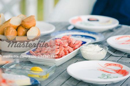Sweden, Vastkusten, Vastra Gotalands lan, Bohuslan, Havstenssund, Set table with shrimps and bread
