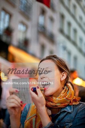 France, Paris, Young woman applying lipstick on city street