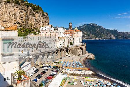 Coastal road with beach umbrellas and lounge chairs on waterfront and the Church of Santa Maria Maddalena in the background, Atrani, Amalfi Coast, Italy
