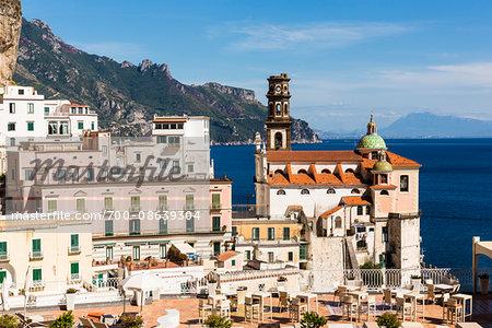 Rooftops of buildings with restaurant patio and the Church of Santa Maria Maddalena, Atrani, Amalfi Coast, Italy