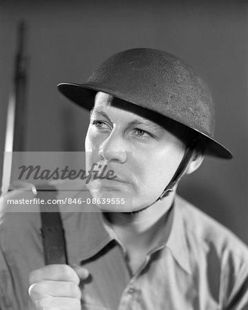 1930s 1940s SERIOUS PORTRAIT AMERICAN SOLDIER IN UNIFORM WEARING BRODIE HELMET USED BY US ARMY THROUGH 1942