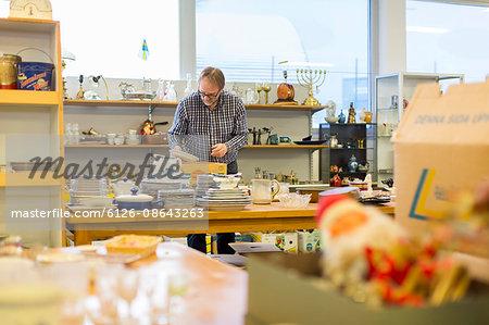 Sweden, Man choosing plates in store