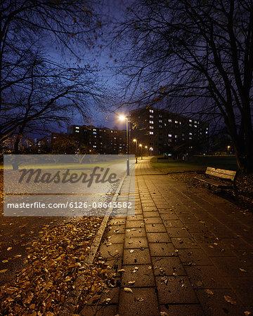 Sweden, Skane, Malmo, Rosengard, Illuminated alley in park at night