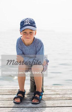 Sweden, Stockholm Archipelago, Grasko, Boy (6-7) sitting on pole on jetty