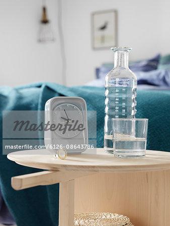 Sweden, Vastergotland, Alarm clock and bottle in bedroom