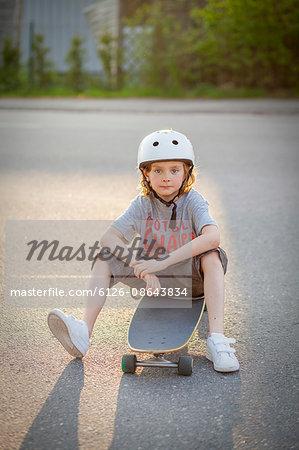 Sweden, Vastergotland, Lerum, Portrait of boy (8-9) sitting on skateboard on street