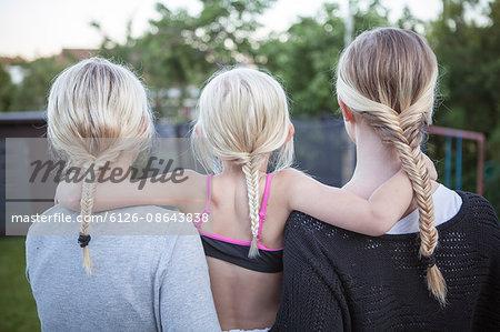Sweden, Vastergotland, Lerum, Rear view of girls (8-9, 16-17) with braided ponytail standing in backyard
