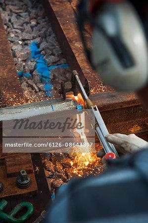 Sweden, Skane, Malmo, Worker repairing railroad track