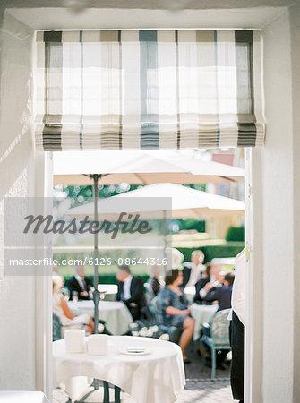 Sweden, People sitting under umbrellas at outdoors restaurant