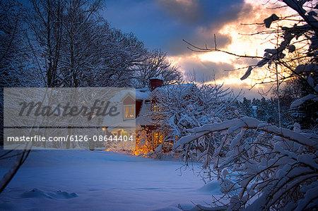 Sweden, Stockholm Archipelago, Uppland, Varmdo, Stromma, Illuminated house in snowy forest