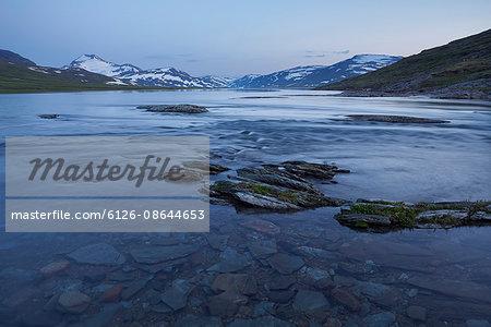 Sweden, Lapland, Padjelanta National Park, Sarjasjaure, lake at dusk, mountain range in background