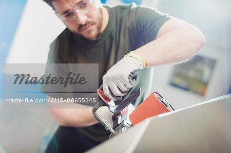 Worker using sander in steel factory