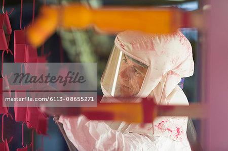 Worker painting steel red in steel factory