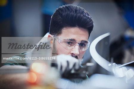 Worker examining pieces in steel factory