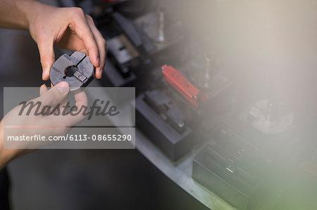 Worker examining part in steel factory