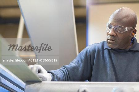 Focused worker sanding steel in steel factory