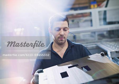 Worker examining steel in steel factory