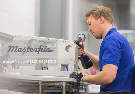 Worker using drill in steel factory