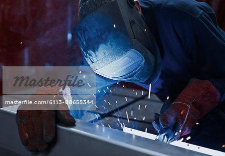 Welder using welding torch in steel factory