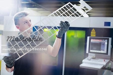 Worker examining piece in steel factory