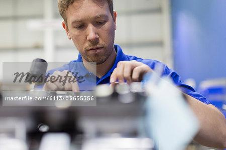 Worker examining machinery in steel factory