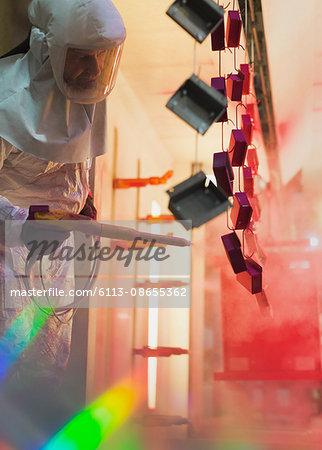 Worker painting steel pieces red in steel factory