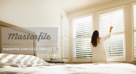 Woman in bathrobe opening bedroom window blinds