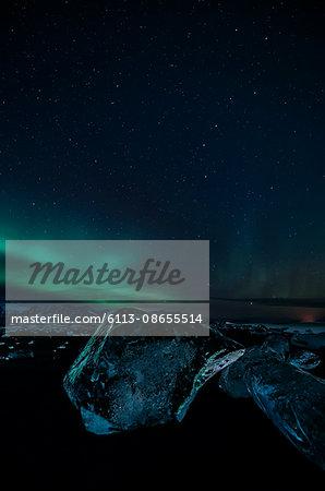 Northern lights over icy night landscape and Jokulsarlon glacier, Iceland