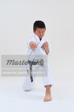 Japanese kid in karate uniform on white background