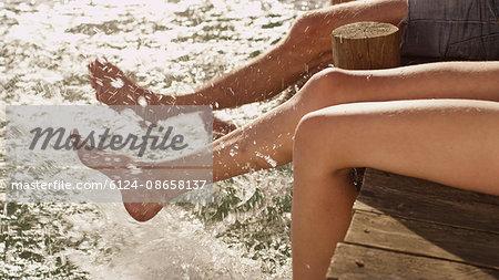 Young couple splashing bare feet in lake