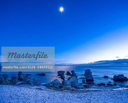 Sweden, Gotland, Holmhallar, Stack rocks at night