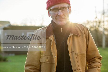Sweden, Vastergotland, Portrait of mature man standing in backyard