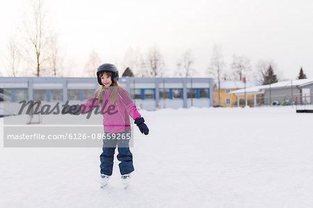 Sweden, Vasterbotten, Umea, Girl (6-7) ice-skating in winter