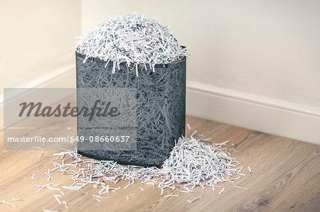Overflowing shredded paper in paper shredder basket