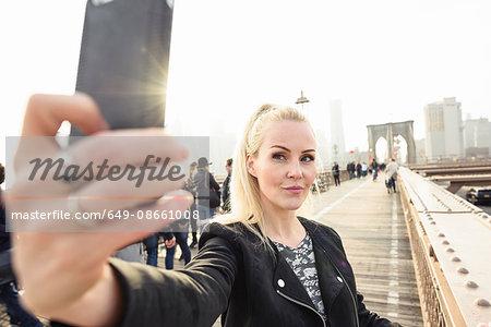 Female tourist taking smartphone selfie on Brooklyn Bridge, New York, USA
