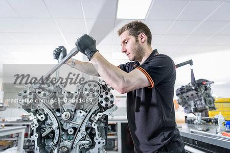 Engineer working on engine in racing car factory