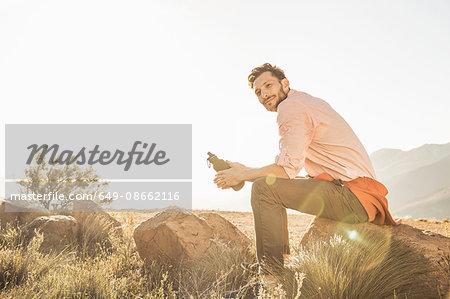 Man sitting on rock in field