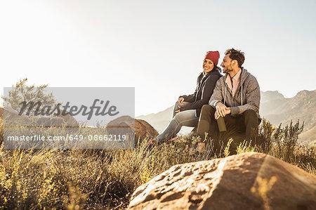 Couple sitting on rocks in field