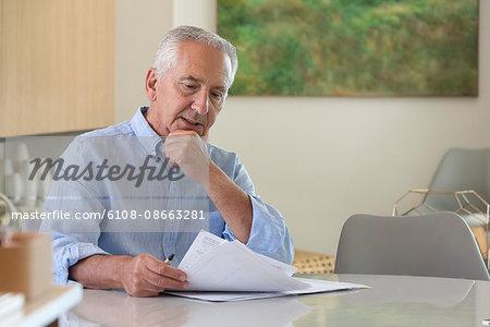 Senior man doing paperwork at home