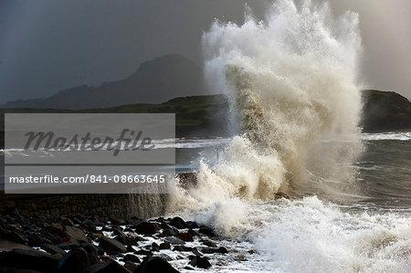 Huge waves crash against a stone jetty at Criccieth, Gwynedd, Wales, United Kingdom, Europe