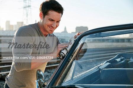 Man polishing car smiling, Los Angeles, California, USA