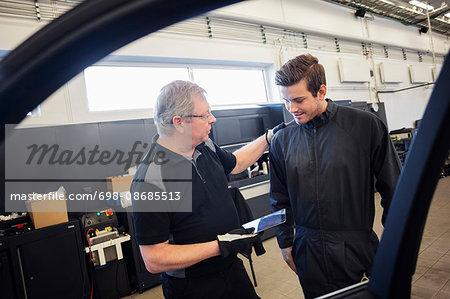 Mechanics using digital tablet seen through car window at auto repair shop