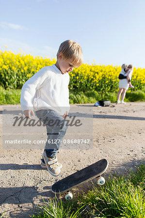 Boy preparing to skateboard on dirt road at rapeseed field