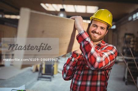 Portrait of carpenter carrying wooden plank in workshop