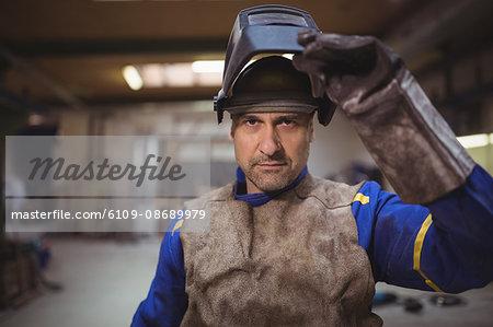 Worker touching helmet in the workshop