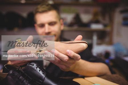 Cobbler holding a shoe tree in workshop